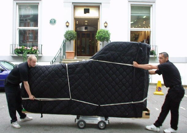 Piano Moving & Piano Storage , two movers moving a concert grand piano